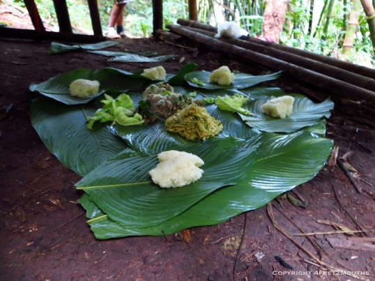 Lunch on banana leaves below a rattan hut