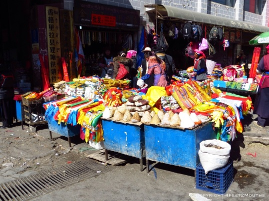 Market vendors with cheese and prayer flags