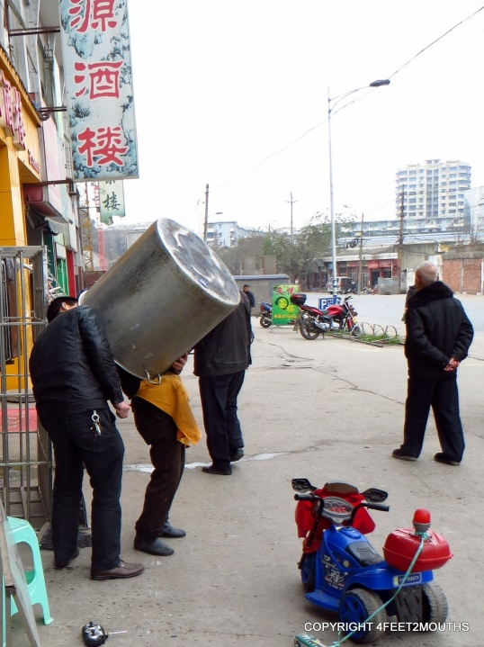 Two men clean a big pot on the street