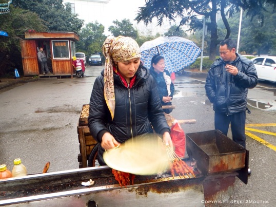 Uyghur woman fans coals alas she grills shish kabobs